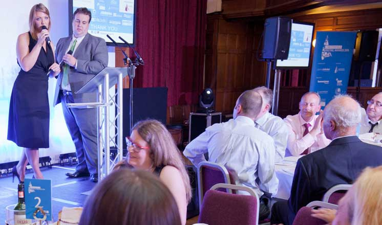 Round tables filled with people as two hosts stand on the stage at the Chesterfield Retail Awards at the Winding Wheel.