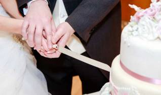 A bride and groom's hands as they cut the wedding cake.