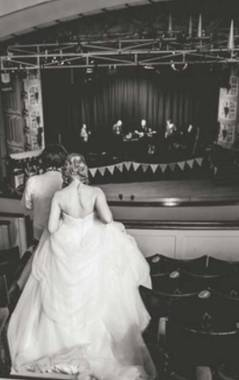 A bride and groom in the circle at the Winding Wheel as a band plays on the stage below.