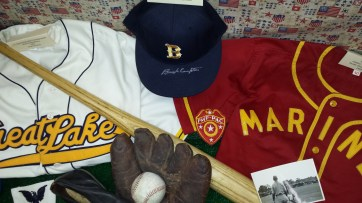 """The mitt is a U.S. Navy stamped glove from WWII. The ball cap is a 1980s vintage UCLA team cap that was signed by Bruins HoF catcher, LT. Lynn """"Buck"""" Compton (Co. E, 506th PIR, 101st A/B)."""