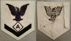 """Specialist """"A"""" rating badge (athletic instructor) for a third class petty officer. This was applied to the dress/undress white uniform and dates from World War II. Note the reverse and the extra material folded and stitched flat as it was cut down to conceal the other chevrons. All rating badges typically are made as first class and cut to meet the rate (rank) of the sailor."""