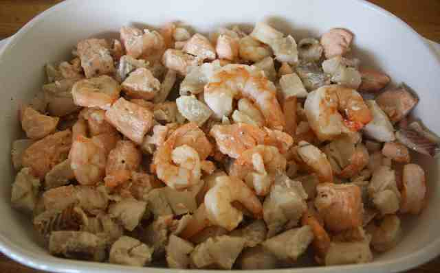 Seafood Gratin. Easy dish of poached salmon, cod and prawns topped with scalloped potatoes and cheese which is ready in under 30 minutes.