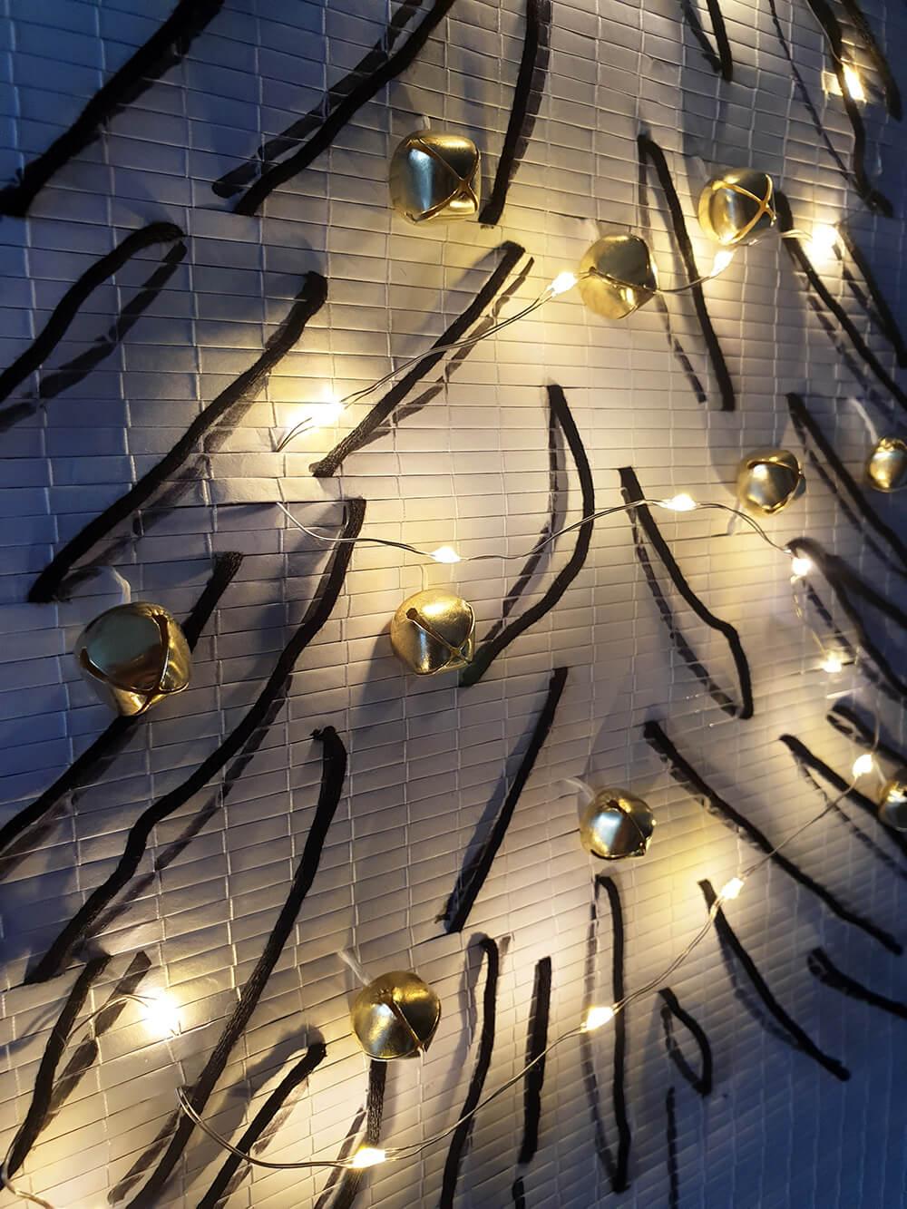 sapin dessiné et décoré avec des grelots et une guirlande led - DIY Noël : comment fabriquer un sapin zéro déchet ?