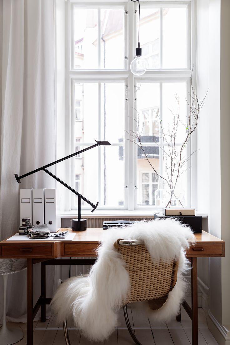 bureau en bois devant fenetre avec fauteuil en osier - Comment aménager un coin bureau efficace à la maison?
