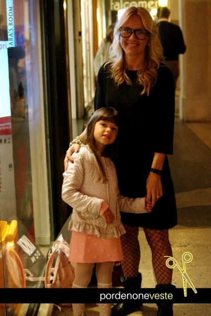 La super mamma conquista Corso Vittorio con un total black total: vestito, occhiali con la montatura spessa, calze a rete nere.
