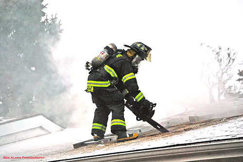 firefighter cutting into a roof