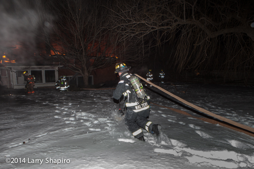 fireman pulls hose through snow at night house fire