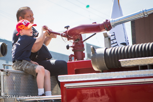 young boy helps with fire engine