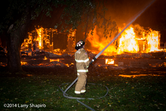 fireman at night with hose line against a backdrop of fire