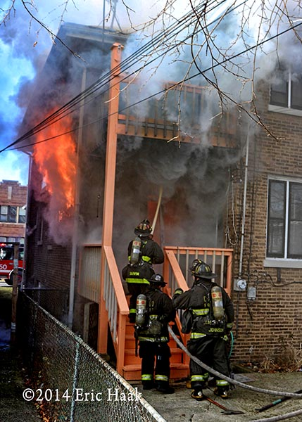 firemen with hose enter house with flames