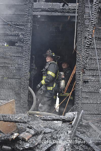 firemen overhaul fire scene