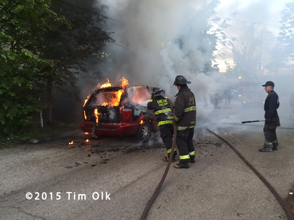 firemen extinguish a minivan engulfed in flames