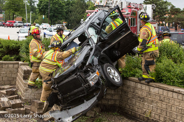 SUV tangles over retention wall after crash