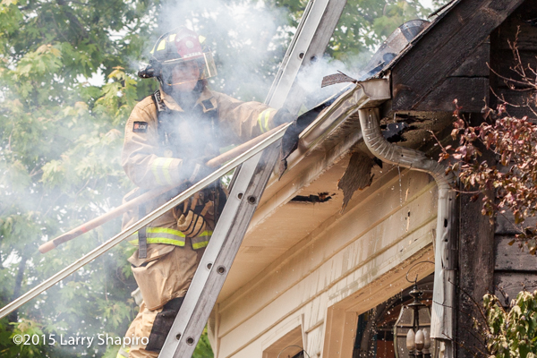 female firefighter on ladder at fire scene