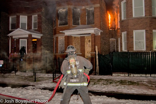firefighter pulls hose a building burns at night