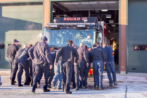 firemen push new fire engine into station