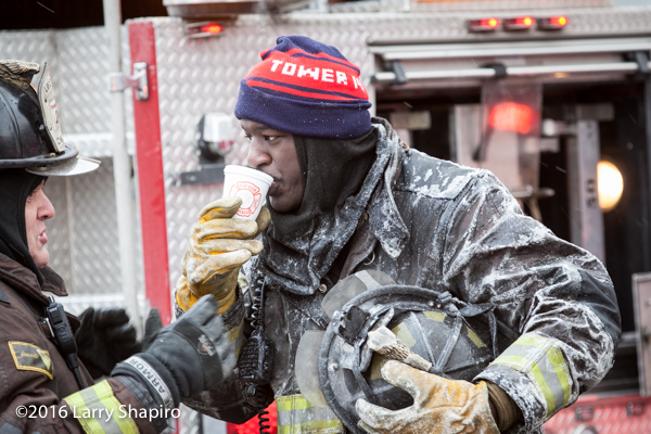 firefighter covered with ice drinking coffee