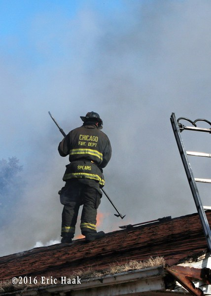 A Chicago firefighter vents the roof at house fire