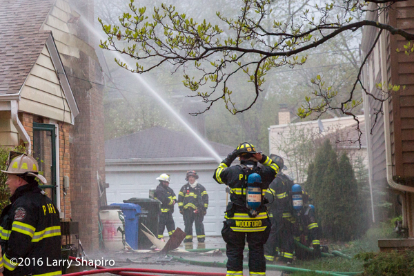 firefighters with hose line at fire scene