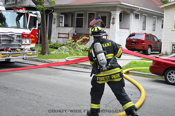 firefighter stretches hose inn the street