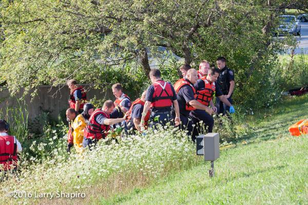 firefighter paramedics carry a patient up a hill