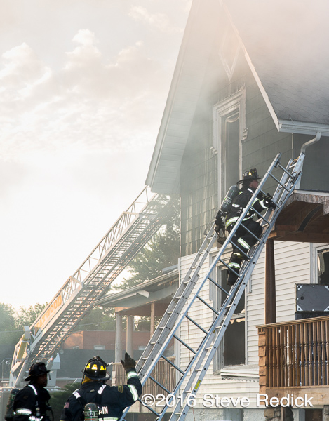 firefighters climb ground ladder at fire