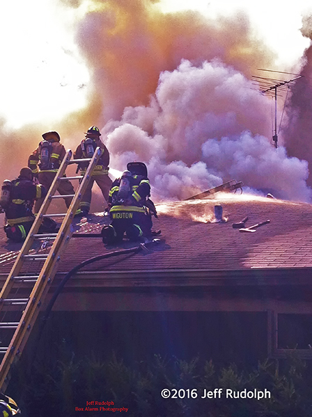 firefighters on house roof with heavy smoke