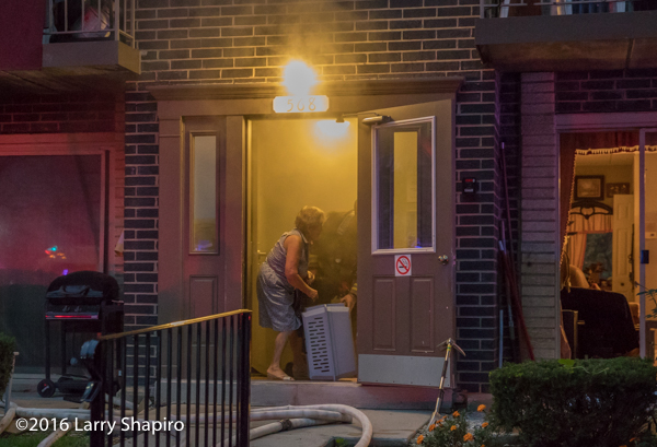 firefighter assistes elderly resident with pet during fire