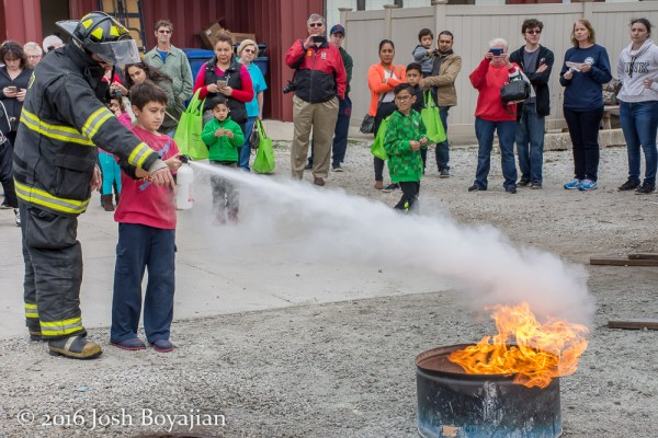 child learning to use a fire extinguisher