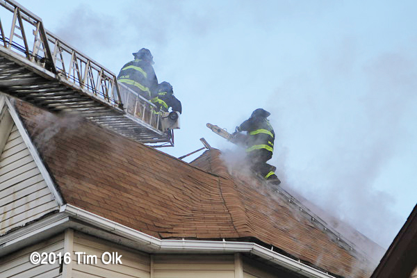 Firefighter venting a house roof