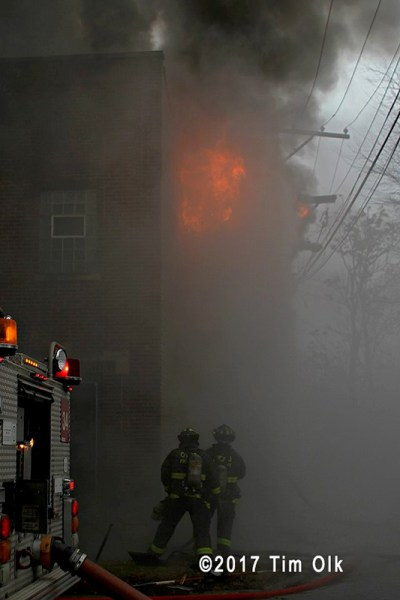 heavy flames blow out of building on fire