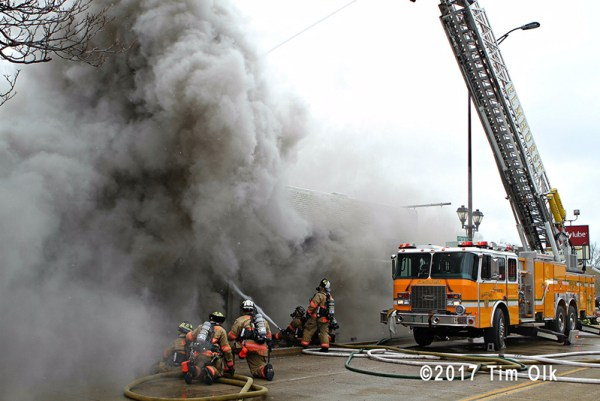 heavy smoke pushes from commercial building fire