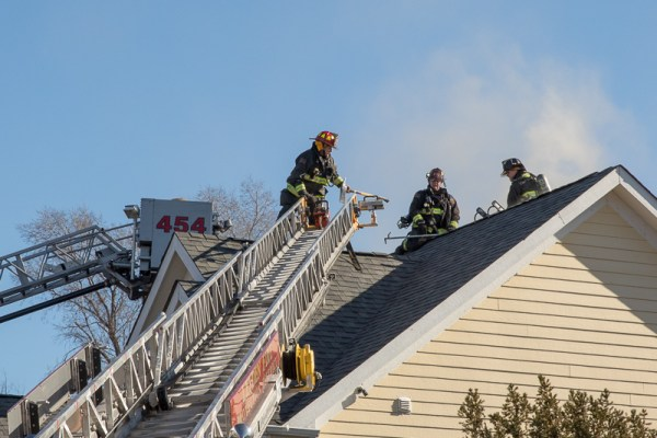 firefighters on roof of fire building
