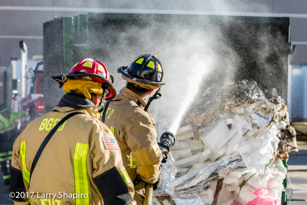 Firefighters with hose dousing dumpster fire