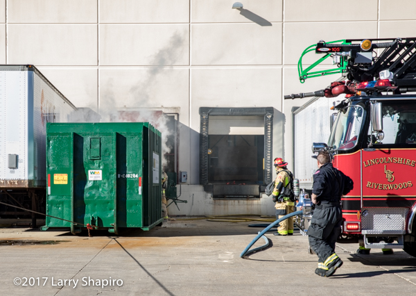dumpster fire alongside a building
