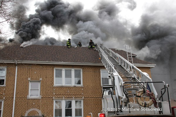 firefighters on peak roof to vent fire with heavy smoke