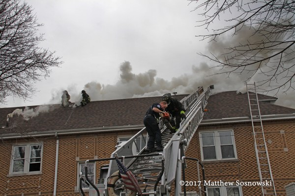 firefighters climb aerial ladder at fire