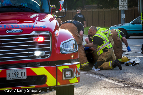 paramedics aid patient in street after crash