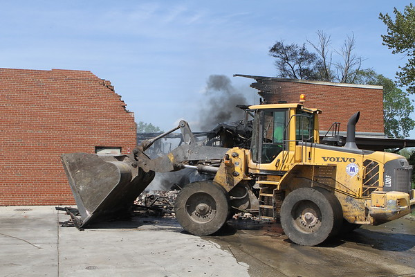 end loader clearing debris after a fire