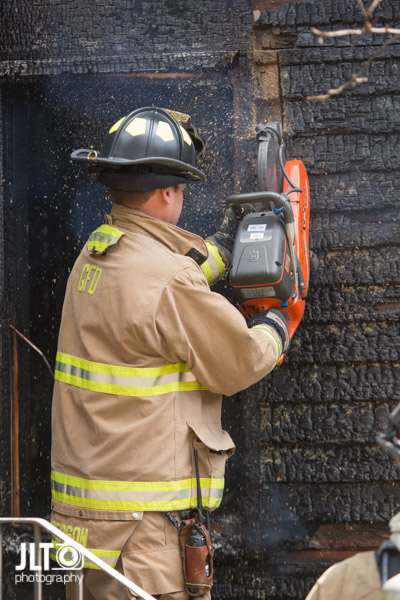 firefighter with saw after house fire