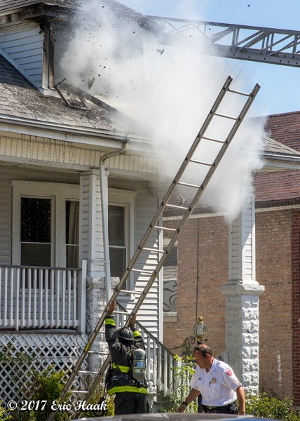 firefighters raise a ground ladder at a house fire