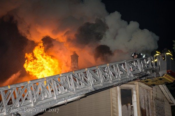 heavy flames and smoke through roof of a house at night