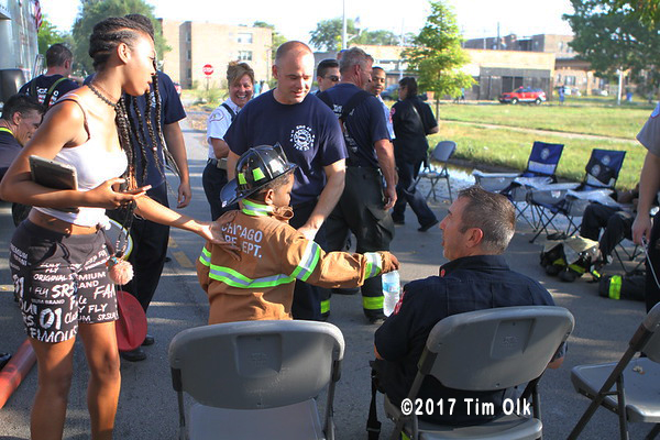 young boy offers a drink to a firefighter