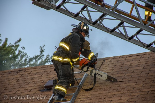 Firefighter vents roof with a saw