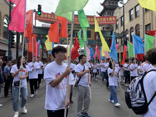 照片九:學生學者聯誼會的學生們高舉70面彩旗緩緩通過主席臺前