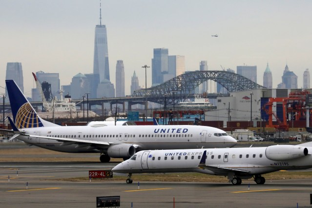 United Airlines passenger jets taxi with New York City as a backdrop