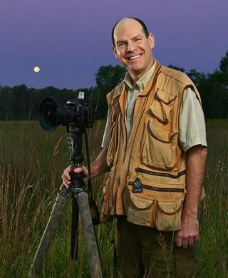Mike MacDonald stands in the prairie at a cusp in time, as the full moon sets and a new day begins.
