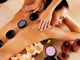Adult woman having hot stone massage in spa salon. Beauty treatm