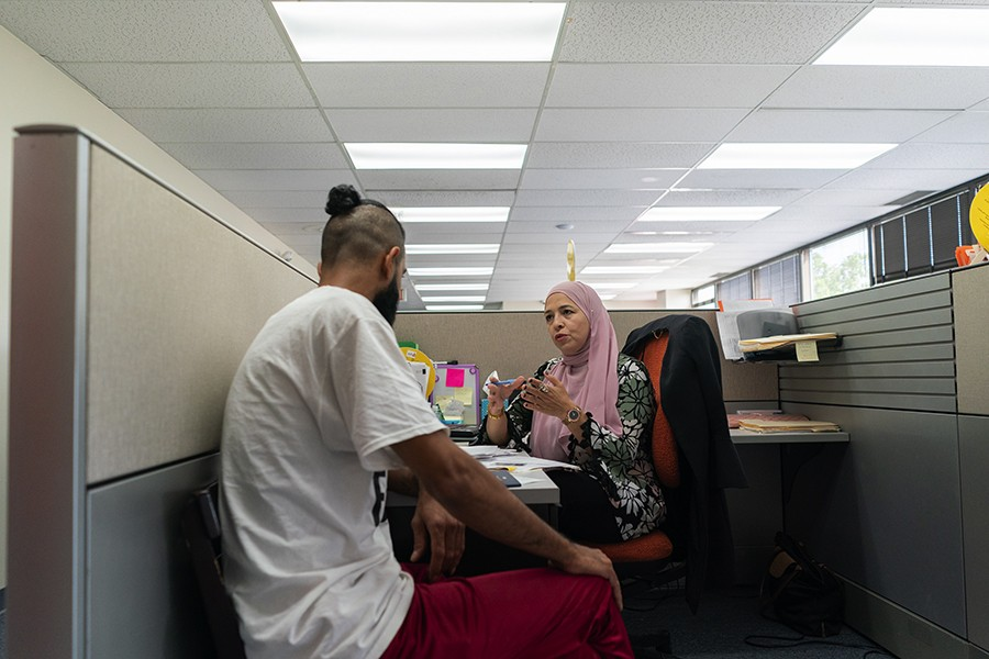 Fouzia Othman works with a client at the Arab American Family Services office. Case managers help community members with translating mail, applying for WIC and SNAP benefits, immigration paperwork, and other needs.