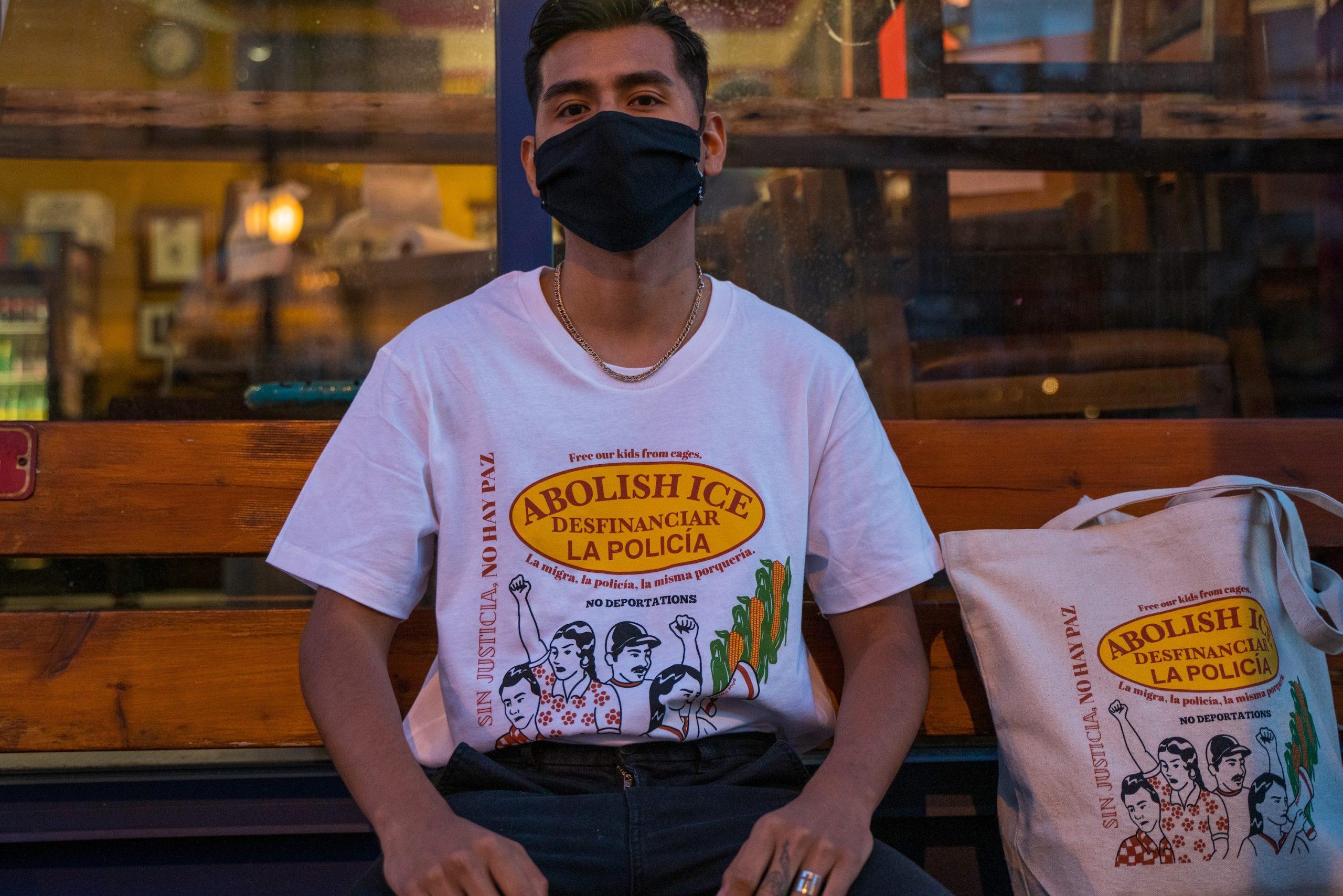 Fernando Delgado shows off his T-shirt and tote bag.